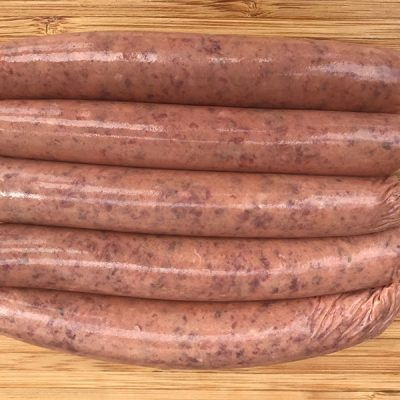 Thin beef sausages laid out on a timber board ready to cook